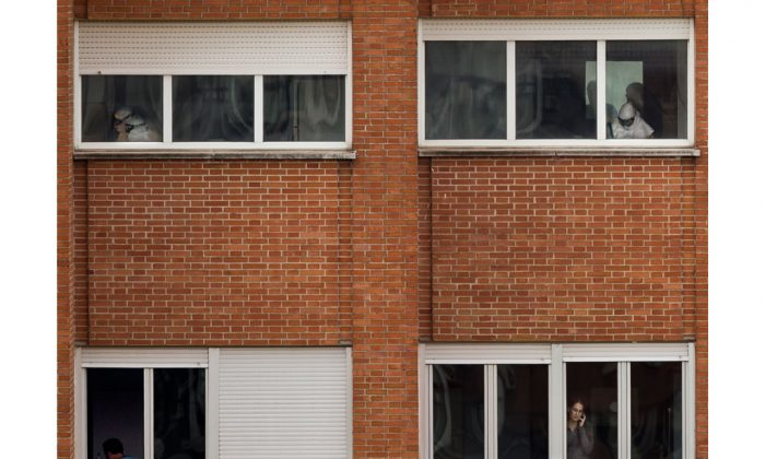 """Medical practitioners wearing protective clothing work while Javier Limon, the husband of the nursing assistant infected with Ebola, is seen through a window, down left, while another isolated girl talks on her phone inside an isolated ward on the sixth floor of the the Carlos III hospital in Madrid, Spain, Friday, Oct. 10, 2014. A Spanish hospital official says the nursing assistant infected with Ebola is """"stable,"""" hours after authorities described her condition as critical. She is the first person known to have caught the disease outside the outbreak zone in West Africa. She contracted the virus while helping treat a Spanish missionary who became infected in West Africa, and later died. (AP Photo/Daniel Ochoa de Olza)"""