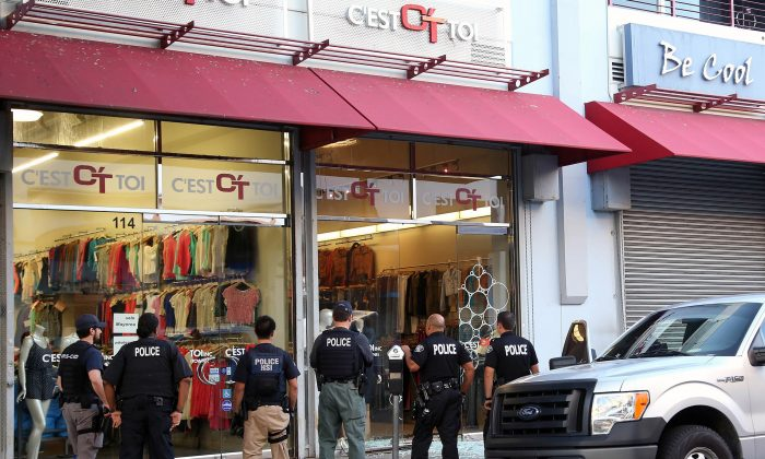 Law enforcement agents stand outside a clothing store after a raid in the Los Angeles Fashion District, on Sept. 10, 2014. Federal authorities on Thursday, Oct. 2, 2014, slapped new financial reporting rules on 2,000 businesses in the fashion district of Los Angeles in an effort to curtail suspected Mexican drug money laundering. (AP Photo/Nick Ut)