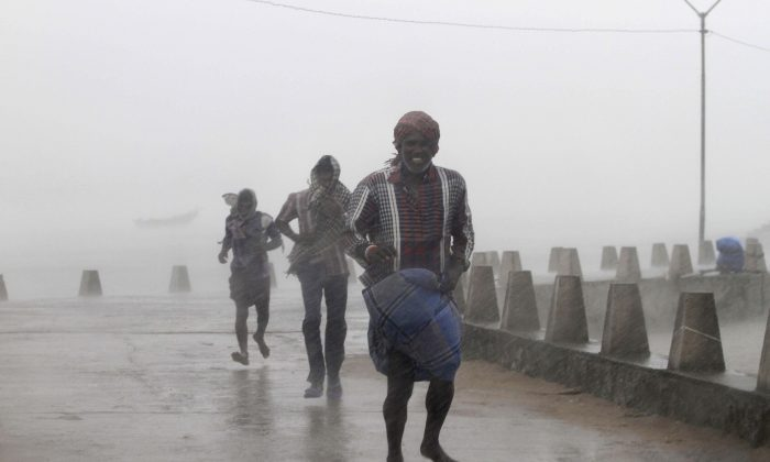 People run for shelter as heavy rain and wind gusts rip through the Bay of Bengal coast at Gopalpur, Orissa, about 285 kilometers (178 miles) north east of Visakhapatnam, India, Sunday, Oct. 12, 2014. Trees were uprooted and power cables snapped as a powerful cyclone swept through the Bay of Bengal and slammed into the southern city of Visakhapatnam, one of two storms pounding Asia on Sunday. (AP Photo/Biswaranjan Rout)