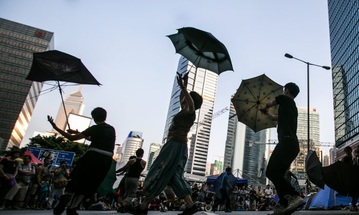Pro-democracy activists perform a choreographed umbrella dance to music in the central District of Hong Kong on Oct. 12, 2014. (Benjamin Chasteen/Epoch Times)