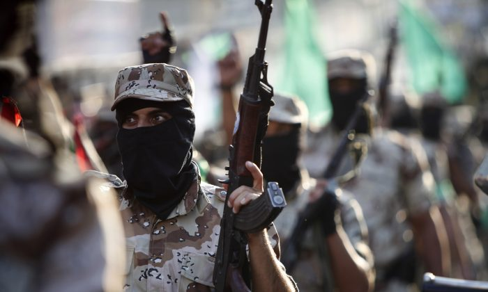 FILE - In this Nov. 14, 2013 file photo, masked Palestinian members of the military wing of Hamas carry their weapons while chanting slogans during a parade to mark the anniversary of a 2012 battle against Israel in Gaza City. The chaos unleashed by the Arab Spring has led to the rise of powerful militias -- including many Islamic extremist groups -- across a Middle East where many central governments have been exposed as weak. Some of the groups are allied with such governments, others are fighting to topple them and some -- like the Kurdish peshmerga in northern Iraq -- are seen as vital Western allies. All could prove to be major obstacles to bringing peace or stability to the troubled region. (AP Photo/Adel Hana, File)