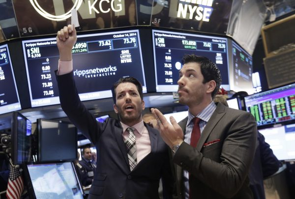 "Jonathan Scott (L) and Drew Scott, of HGTV's ""Property Brothers"" cable television show, mimic traders as they visit the post that handles Scripps Networks Interactive, on the floor of the New York Stock Exchange, after ringing the opening bell, Tuesday, Oct. 14, 2014. (AP Photo/Richard Drew)"