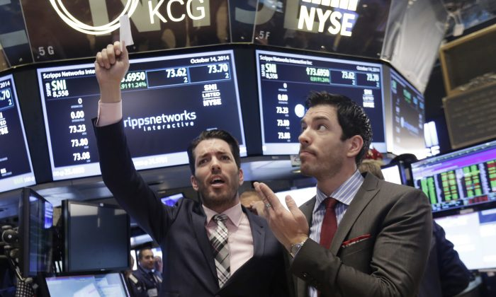 """Jonathan Scott (L) and Drew Scott, of HGTV's """"Property Brothers"""" cable television show, mimic traders as they visit the post that handles Scripps Networks Interactive, on the floor of the New York Stock Exchange, after ringing the opening bell, Tuesday, Oct. 14, 2014. (AP Photo/Richard Drew)"""