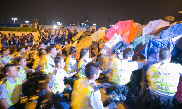 Police start to beat pro-democracy protesters after they successfully shutdown Lung Wo Road, one of the major roadways in Hong Kong, on Oct. 14, 2014. (Benjamin Chasteen/Epoch Times)