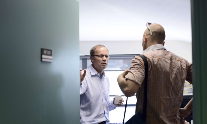 Laureate of the 2014 Nobel Memorial Prize in Economic Sciences, French economist Jean Tirole (C), in his office at the Toulouse School of Economics on Oct. 13, 2014. Tirole is a master of game theory and industrial organization. (Remy Gabalda/AFP/Getty Images)