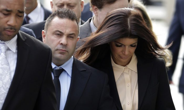 """""""The Real Housewives of New Jersey"""" stars Giuseppe """"Joe"""" Giudice, center, and his wife, Teresa Giudice (R) of Montville Township, N.J., walk toward the Martin Luther King Jr. Courthouse before a court appearance, in Newark, N.J., on Oct. 2, 2014. (Julio Cortez/AP Photo)"""