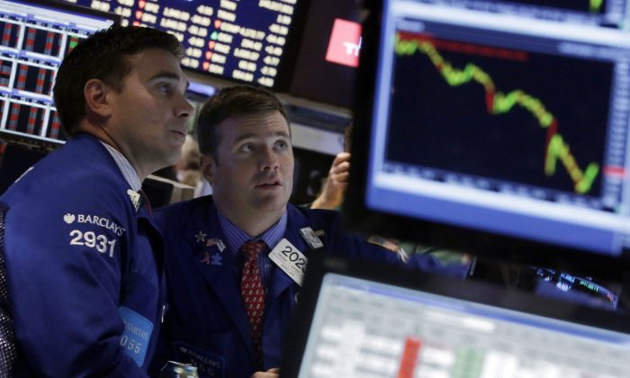 Specialists Robert Tuccillo (L) and Frank Masiello work on the floor of the New York Stock Exchange Wednesday, Oct. 15, 2014. The Dow Jones industrial average plummeted as much as 460 points in afternoon trading, then clawed back much of the ground it lost. It ended down 173 points, or 1.1 percent. (AP Photo/Richard Drew)