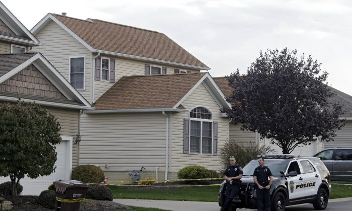 Tallmadge police guard a home in Tallmadge, Ohio Wednesday, Oct. 15, 2014, where Amber Joy Vinson stayed over the weekend before flying home to Dallas. (AP Photo/Mark Duncan)