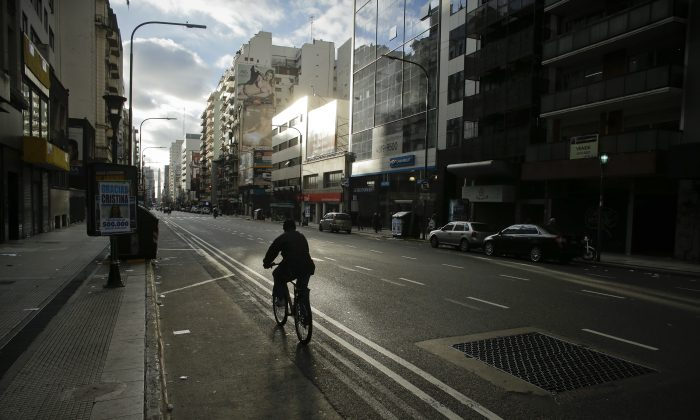 A man rides his bicycle through an empty downtown avenue during a strike in Buenos Aires, Argentina, on Aug. 28, 2014. Just as the US job market has finally strengthened, the Federal Reserve now has to confront a new worry: A sputtering global economy that's spooked investors across the world. (AP Photo/Victor R. Caivano)