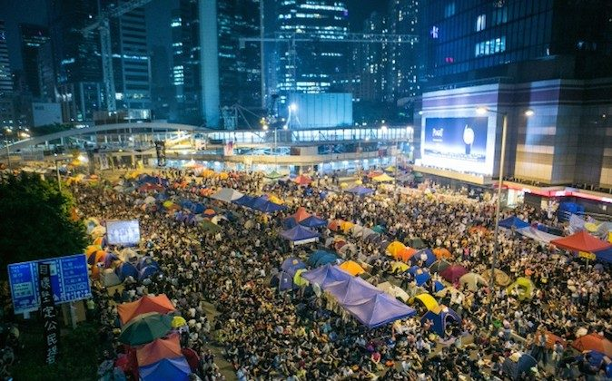 Thousands of pro-democracy protesters attend a rally held by the students leaders after an earlier incident this morning where the police beat protesters with batons, fists, and pepper spray after protesters successfully blocked a road in Hong Kong on Oct. 15, 2014. (Benjamin Chasteen/Epoch Times)