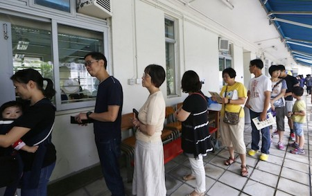People queue up at a polling station on the last day to vote for an unofficial referendum on democratic reform in Hong Kong Sunday, June 29, 2014. (AP Photo/Kin Cheung)