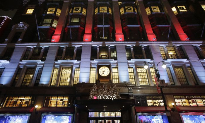 Macy's department store in Herald Square is illuminated with holiday lighting, in New York, Tuesday, Dec. 17, 2013. Macy's Inc. plans to open its stores at 6 p.m. on Thanksgiving Day, two hours earlier than last year. (AP Photo/Mark Lennihan)