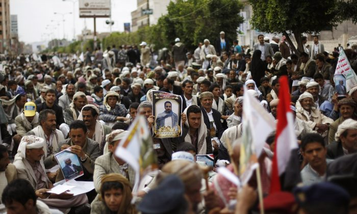 A mourner, center, holds a poster of a man who was killed Thursday by a suicide bomber in central Sanaa, Yemen, Tuesday, Oct. 14, 2014.  Two suicide bombings in Yemen killed nearly 70 people last Thursday, with one targeting an anti-government rally by followers of the Houthi Shiite group,  who control Sanaa.  (AP Photo/Hani Mohammed)