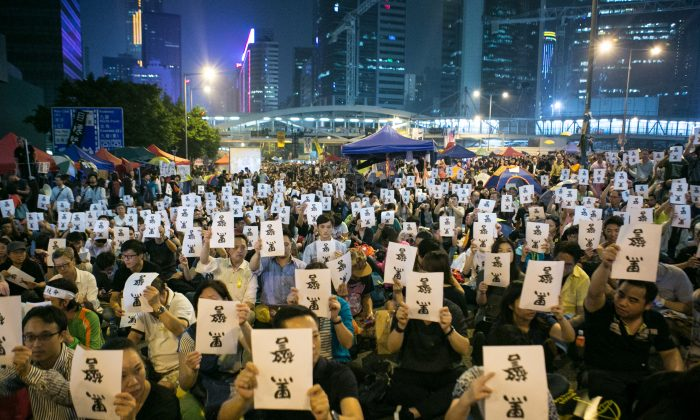 """Thousands of pro-democracy protesters hold signs upside down that say in Chinese """"Black Police,"""" referring to the incident in which police beat and kicked protesters as they removed them from Long Wo Road, on Oct. 15. (Benjamin Chasteen/Epoch Times)"""
