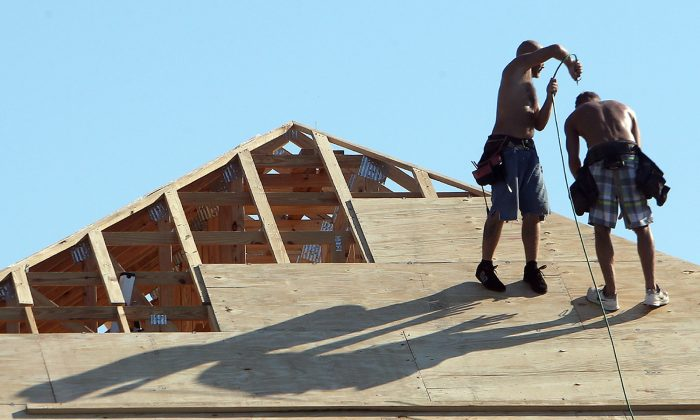 In this Sept. 18, 2014 photo, a construction worker blows compressed air on a fellow worker atop a new home in Panama City Beach, Fla. The Commerce Department reports on U.S. home construction in September on Friday, Oct. 17, 2014. (AP Photo/The News Herald, Andrew Wardlow)