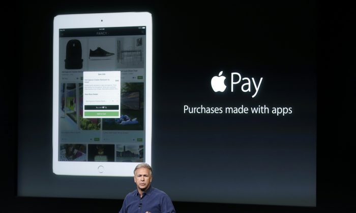 Phil Schiller, Apple's senior vice president of worldwide product marketing, discuss the features of the new Apple iPad Air 2 and Apple Pay during an event at Apple headquarters in Cupertino, Calif. on Thursday, Oct. 16, 2014. (AP Photo/Marcio Jose Sanchez)