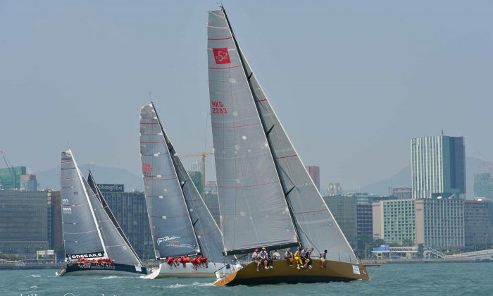 Boats 'FreeFire', 'Team Beau Geste' and 'One Sails East' with the sail of 'mandrake 3' in the background leaving the start line in Victoria Harbor on Thursday Oct 16, 2014 in the Hong Kong to Hainan race. (Bill Cox/Epoch Times)