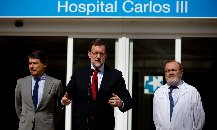 Spanish Prime Minister Mariano Rajoy (C) gives a speech at the front door of Carlos III hospital, watched by Madrid Regional President Ignacio Gonzalez (L) and Carlos III hospital manager Rafael Perez Santamarina (R) where nurse Teresa Romero is being treated for the Ebola virus on Oct. 10, 2014, in Madrid, Spain. Spanish Health Minister Ana Mato confirmed nurse Teresa Romero had tested positive after treating two Ebola patients that had been brought back to the country from Africa. (Gonzalo Arroyo Moreno/Getty Images)