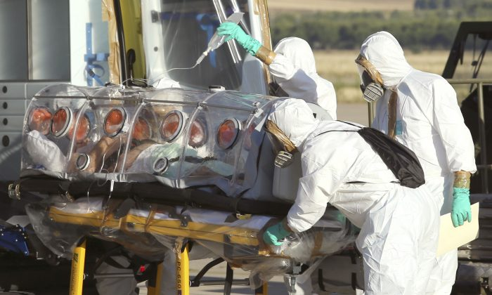 Aid workers and doctors transfer Miguel Pajares, a Spanish priest who was infected with the Ebola virus while working in Liberia, from a plane to an ambulance as he leaves the Torrejon de Ardoz military airbase, near Madrid, Spain, on Aug. 7, 2014. Comparisons between Ebola and AIDS have surfaced in mid-2014 as the Ebola outbreak escalated. But Ebola is not expected to ever be in the same league as AIDS in terms of infections and deaths, said Dr. Anthony Fauci, director of the National Institute of Allergy and Infectious Diseases. (AP Photo/Spanish Defense Ministry, File)