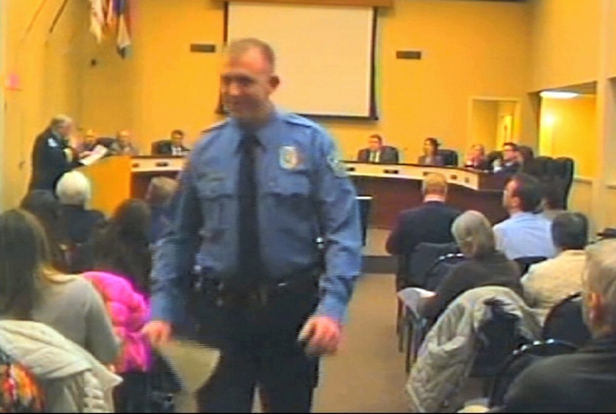 Officer Darren Wilson attends a city council meeting in Ferguson on Feb. 11, 2014. Wilson has told authorities that Michael Brown reached for the gun during a scuffle, the Times reported in a story posted on its website Friday night, Oct. 17, 2014. (AP Photo/City of Ferguson)