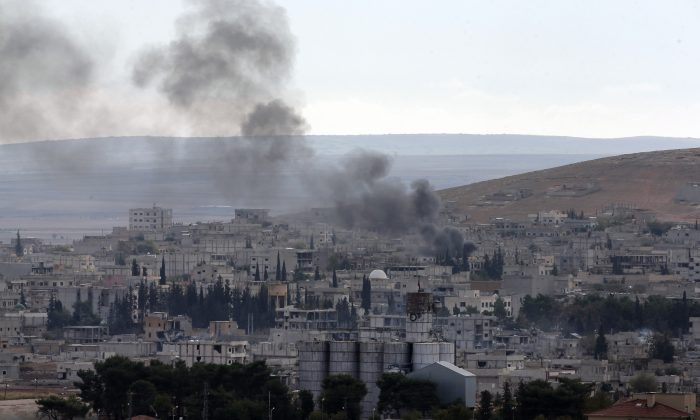 Smoke from a fire rises in Kobani, Syria, while fighting continued between Syrian Kurds and the militants of the Islamic State group, as seen from Mursitpinar on the outskirts of Suruc, at the Turkey-Syria border, Saturday, Oct. 18, 2014. Kobani, also known as Ayn Arab, and its surrounding areas, has been under assault by extremists of the Islamic State group since mid-September and is being defended by Kurdish fighters. (AP Photo/Lefteris Pitarakis)