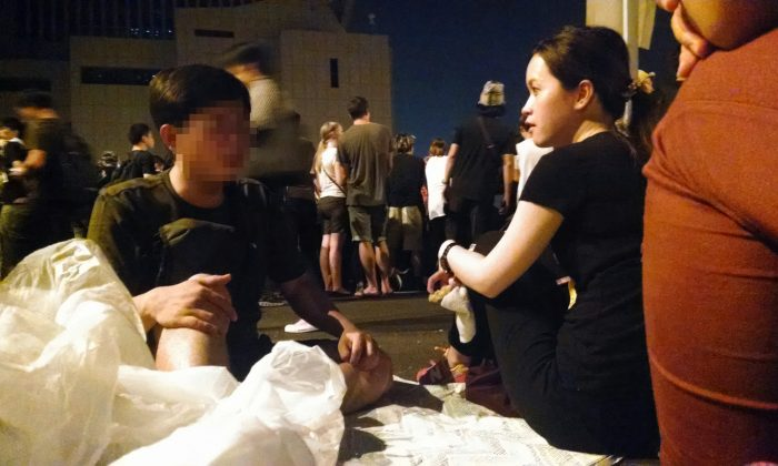 A young mainland Chinese man (left) discusses competing ideas on Hong Kong's democracy with a local Hong Kong woman on Oct. 4, 2014. The occupy movement in Hong Kong has taken over key roads around government offices in an effort to push for greater democracy. (Matthew Robertson/Epoch Times)