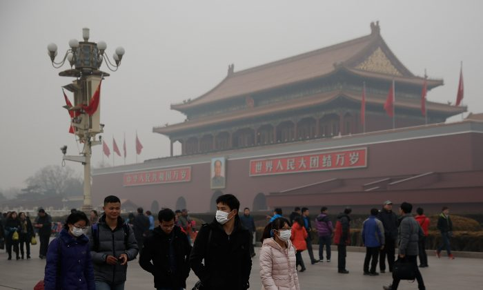 Chinese tourists wear masks on Tiananmen Square during severe pollution on Feb. 25, 2014 in Beijing, China. Top Chinese leaders will get together for the Fourth Plenary Session of the Central Committee of the 18th National Party Congress from Oct. 20 to Oct. 23, 2014. (Lintao Zhang/Getty Images)