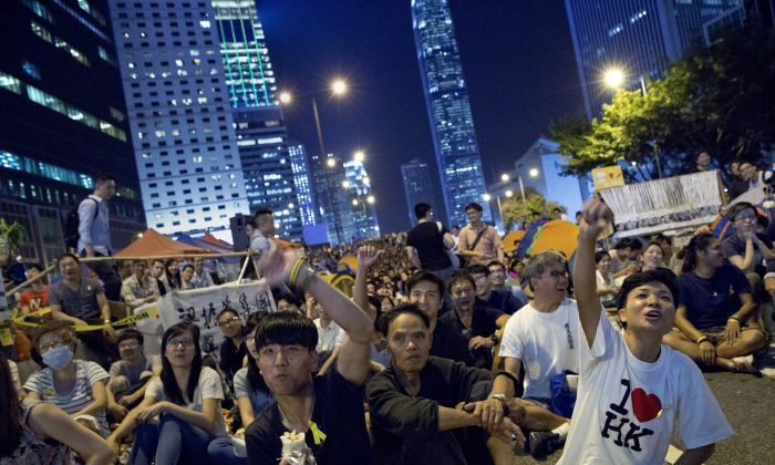 Pro-democracy protesters give thumbs down as they watch a live TV showing talks between Hong Kong government officials and students at an occupied area by the protesters outside the government headquarters in Hong Kong's Admiralty district,Tuesday, Oct. 21, 2014.  (AP Photo/Vincent Yu)