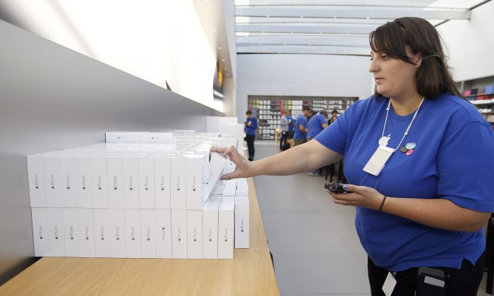 An Apple employee grabs an iPhone 6 for a customer at the Apple Store during the launch and sale of the new iPhone 6 and 6 Plus smartphones, in Palo Alto, Calif., on Sept. 19, 2014. Apple on Monday, Oct. 20, 2014 said it sold 39.3 million iPhones in the last quarter, or 16 percent more than a year ago, which is a record for the quarter. That's partly due to excitement over new iPhone 6 and 6 Plus models that Apple began selling last month. (AP Photo/Tony Avelar)