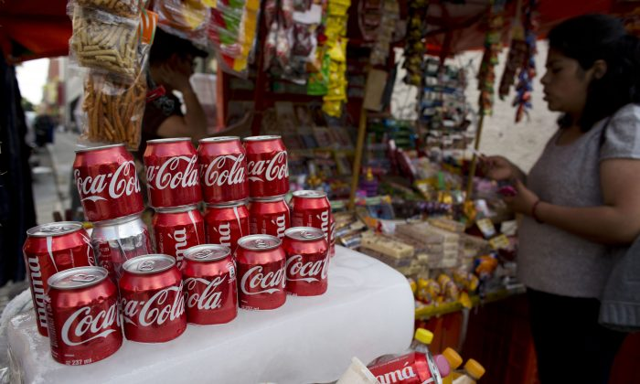 Cans of Coca-Cola sit on an ice block to keep cool at a street vendor's stand in Mexico City on Oct. 9, 2014. Coca-Cola Co. reports quarterly financial results before the market opens Tuesday, Oct. 21, 2014. (AP Photo/Rebecca Blackwell)