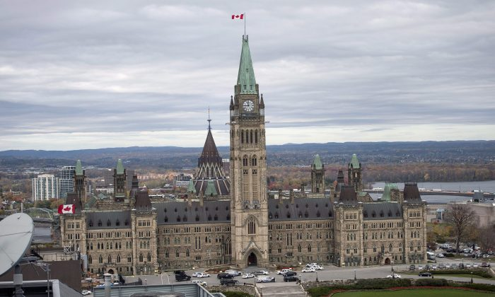 Police surround Parliament Hill in Ottawa on Wednesday Oct. 22, 2014.  A soldier standing guard at the National War Memorial was shot by an unknown gunman and people reported hearing gunfire inside the halls of Parliament. Prime Minister Stephen Harper was rushed away from Parliament Hill to an undisclosed location, according to officials. (AP Photo/The Canadian Press, Justin Tang)