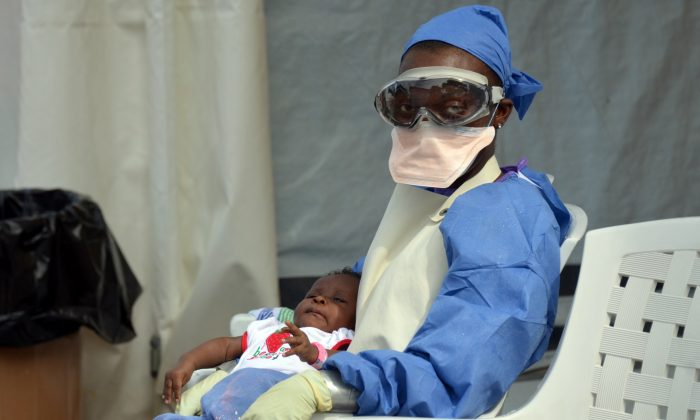 A Liberian health worker holds a baby infected with the Ebola virus on Oct. 18, 2014, at the NGO Medecins Sans Frontieres (Doctors Without Borders) Ebola treatment center in Monrovia. The death toll in the world's worst-ever Ebola outbreak has shot past 4,800, killing at least half of the more than 9,900 people infected. (Zoom Dosso/AFP/Getty Images)