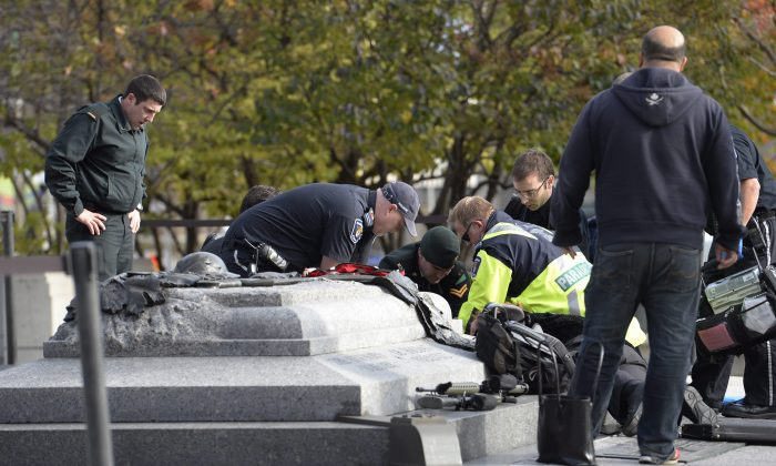 Emergency personnel tend to a soldier shot at the National Memorial near Parliament Hill in Ottawa on Wednesday Oct. 22, 2014.  The soldier was standing guard when an unknown gunman shot him. The gunman reportedly ran towards Parliament Hill, which is currently under lockdown and surrounded by security.  Prime Minister Stephen Harper was rushed away from the building to an undisclosed location, officials in his office said. (AP Photo/The Canadian Press, Adrian Wyld)