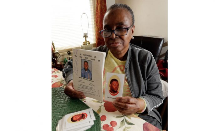 June Broer displays a funeral program and a prayer card featuring images of her only son, Mark Johnson, in Paterson, N.J., Oct. 18, 2014. For days Johnson demanded medical care from jail guards at Rikers Island as he continued to have bloody stools before he died of a bacterial infection in his stomach and small bowel. (AP Photo/Julio Cortez)