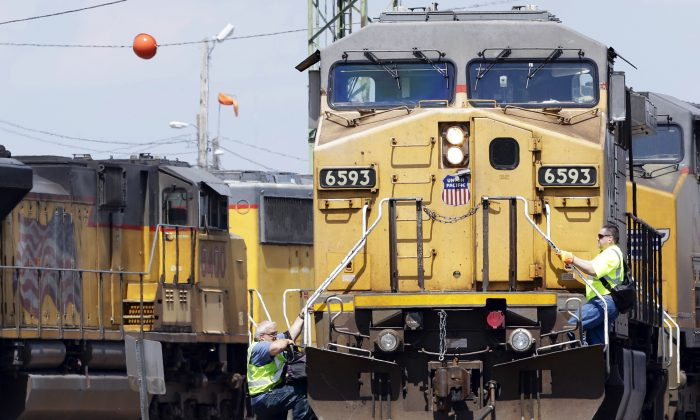 A train (L) operator dismounts a Union Pacific locomotive while another operator climbs up, at a rail yard in Council Bluffs, Iowa., on June 6, 2014. (AP Photo/Nati Harnik)