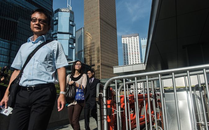 Civil servants walk past a barricade set up and reopened by pro-democracy protestors near the government headquarters as they return to work in Hong Kong on October 6, 2014. Hong Kong has been plunged into the worst political crisis since its 1997 handover as pro-democracy activists take over the streets following China's refusal to grant citizens full universal suffrage. (Anthony Wallace/AFP/Getty Images)