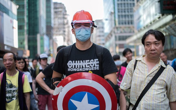 """A man wearing protective gear and carrying a shield from the """"Captain America"""" comic book series stands guard next to a pro-democracy protest barricade in the Mongkok district of Hong Kong on Oct. 19, 2014. (Alex Ogle/AFP/Getty Images)"""