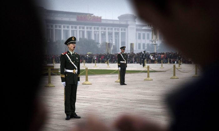 A Chinese paramilitary soldier yawns as he stands at attention while guarding in Tiananmen Square on Oct. 20, 2014 in Beijing, China. (Kevin Frayer/Getty Images)