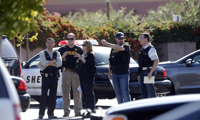 Law enforcement officers gather at the site where a Sacramento County Sheriff's deputy was shot by an assailant who then carjacked two vehicles prompting a manhunt in Sacramento, Calif., Friday, Oct. 24, 2014. (AP Photo/Rich Pedroncelli)