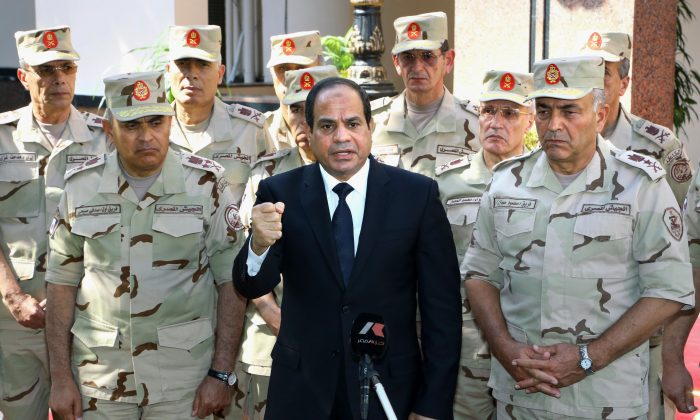 "Egyptian President Abdel-Fattah el-Sissi (C) speaks in front of the state-run TV ahead of a military funeral for troops killed in an assault in the Sinai Peninsula, as he stands with army commanders in Cairo, Egypt, Saturday, Oct. 25, 2014. El-Sissi appeared on the state-run TV and said a deadly assault on an army checkpoint in the Sinai Peninsula that killed 30 troops was a ""foreign-funded operation."" No group has yet claimed responsibility for the attack. (AP Photo/MENA, Mohammed Samaha)"