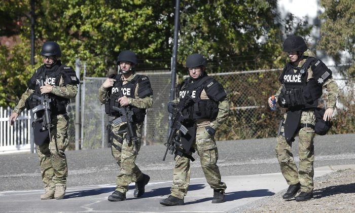 Law enforcement officers dressed in tactical gear leave the Gold County Fairgrounds to help in the search of an assailant, in Auburn, Calif., who shot three sheriff's deputies in two Northern California Counties, Friday, Oct. 24, 2014.  (AP Photo/Rich Pedroncelli)