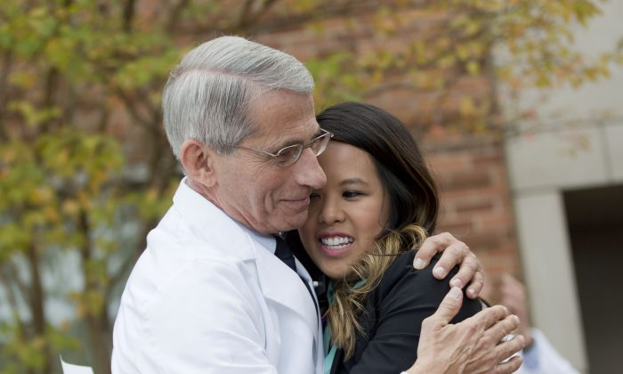 Patient Nina Pham is hugged by Dr. Anthony Fauci, director of the National Institute of Allergy and Infectious Diseases, outside of National Institutes of Health (NIH) in Bethesda, Md., Friday, Oct. 24, 2014. Pham survived  Ebola after treatment at the NIH Clinical Center.  (AP Photo/Pablo Martinez Monsivais)