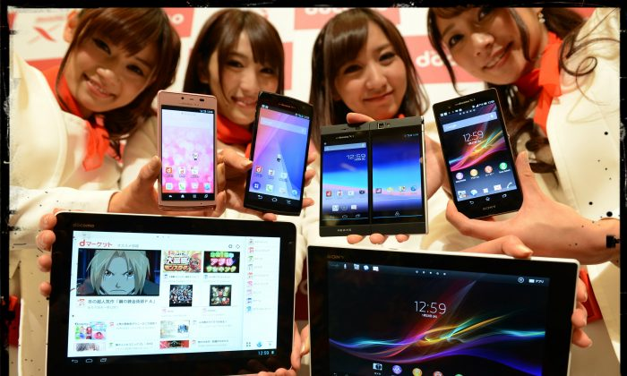 Models show off NTT Docomo's new smartphones (top from L; Aquos Phone EX, Arrows X, Medias W and Xperia Z) and tablets (lower from L; Xperia Tablet Z and 'dtab') during the company's 2013 Spring lineup press preview in Tokyo on January 22, 2013. (Toshifumi Kitamura/AFP/Getty Images; effects added by Epoch Times)