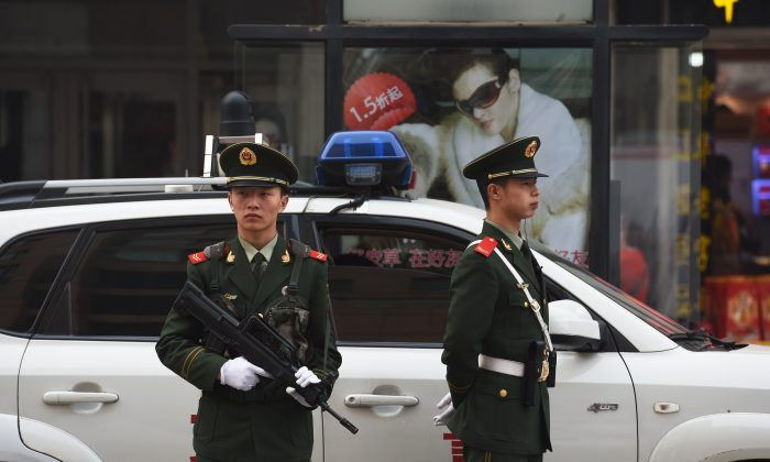 Chinese police officers watch over pedestrians in the Wangfujing shopping district in Beijing on Oct. 24, 2014. (Greg Baker/AFP/Getty Images)