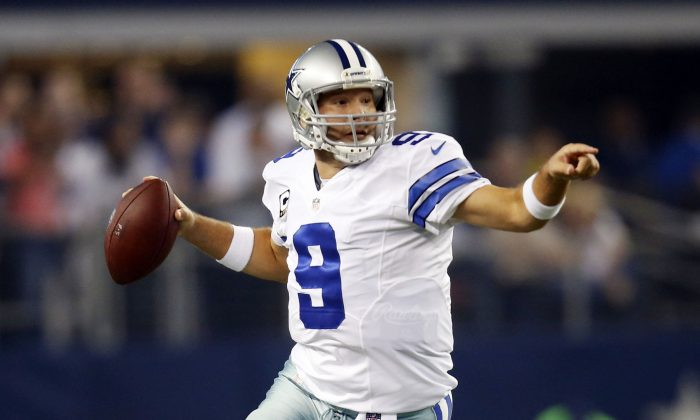 Dallas Cowboys quarterback Tony Romo directs his receivers as he scrambles out of the pocket during the first half of an NFL football game against the Washington Redskins, Monday, Oct. 27, 2014, in Arlington, Texas. (AP Photo/Tim Sharp)