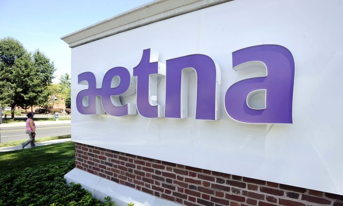 A pedestrian walks past a sign for Aetna Inc., at the company headquarters in Hartford, Conn. Aetna reports quarterly financial results on Tuesday, Oct. 28, 2014. (AP Photo/Jessica Hill)