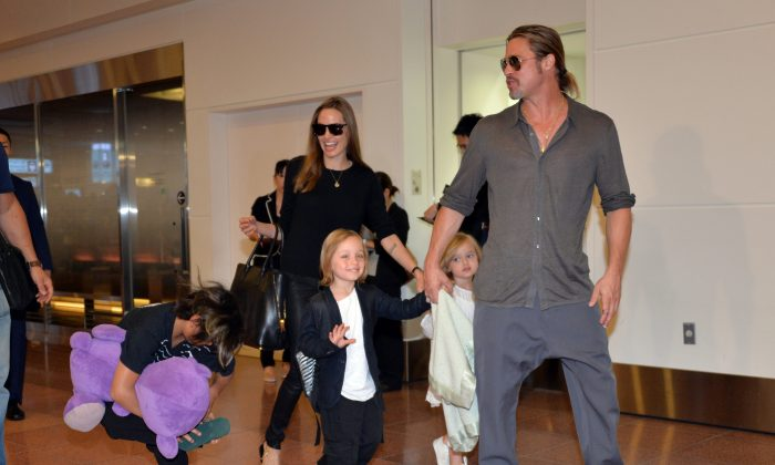 US film stars Brad Pitt (R) and Angelina Jolie (C), accompanied by some of their children, arrive at Haneda International Airport in Tokyo on July 28, 2013. Jolie and Pitt agreed to a temporary custody agreement involving their six children on Sept. 30. (AFP/Getty Images)