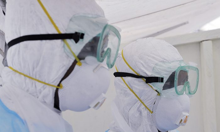 Kenyan medical workers from the Infection Prevention and Control unit wearing full protective equipment are pictured as they show on Oct. 28, 2014, how to handle an infected Ebola patient on a portable negative pressure bed at the Kenyatta national hospital in Nairobi. (Simon Maina/AFP/Getty Images)