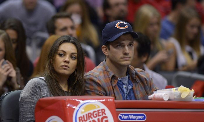 Actors Mila Kunis, left, and Ashton Kutcher watch the Los Angeles Clippers play the Detroit Pistons during the second half of an NBA basketball game, Saturday, March 22, 2014, in Los Angeles. (AP Photo/Mark J. Terrill)