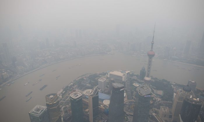 A general view shows the skyline of the Lujiazui Financial District in Pudong, seen from the 109th floor of the Shanghai Tower (still under construction), covered in smog in Shanghai on Oct. 16. Associates of former Chinese leader Jiang Zemin, including Feng Jun, general manager of State Grid Shanghai Municipal Electric Power Company, are under investigation on a charge of corruption. (Johannes Eisele/AFP/Getty Images).